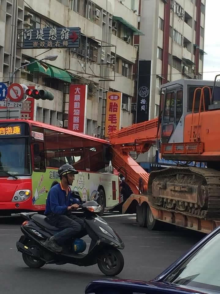 聯結車載挖土機要轉彎,不料挖土機臂擊中旁邊的公車。圖/讀者提供