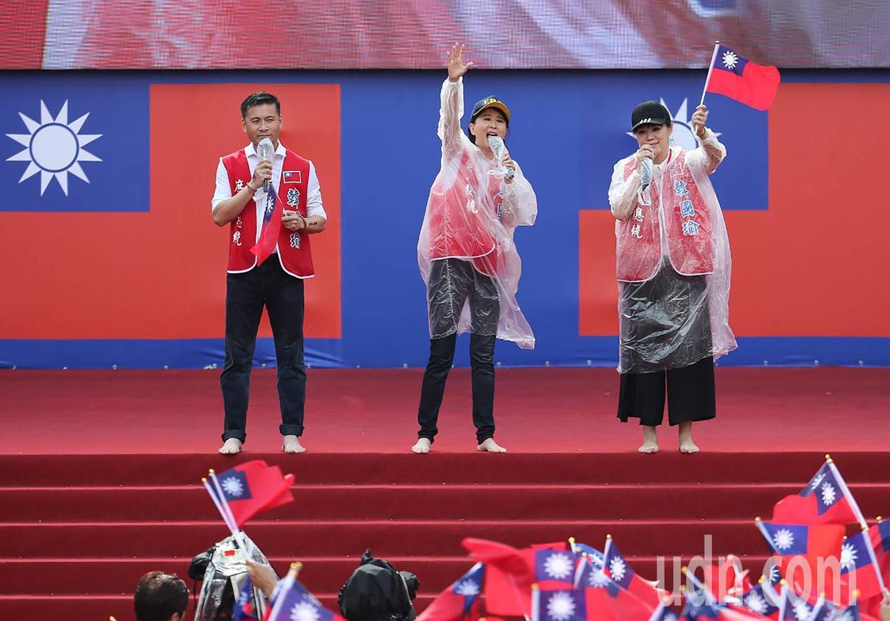 主持人台北市議員王鴻薇(中)、戴錫欽(左)等上台時脫下鞋子在滂沱大雨中要以最接地...