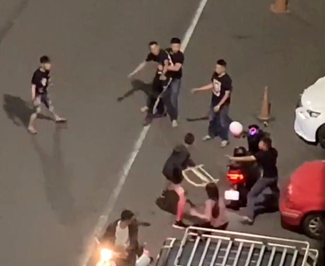 高雄市三民區2男子在馬路上大打出手,其中1人拿椅要打對方被朋友拉住。圖/擷自「爆...