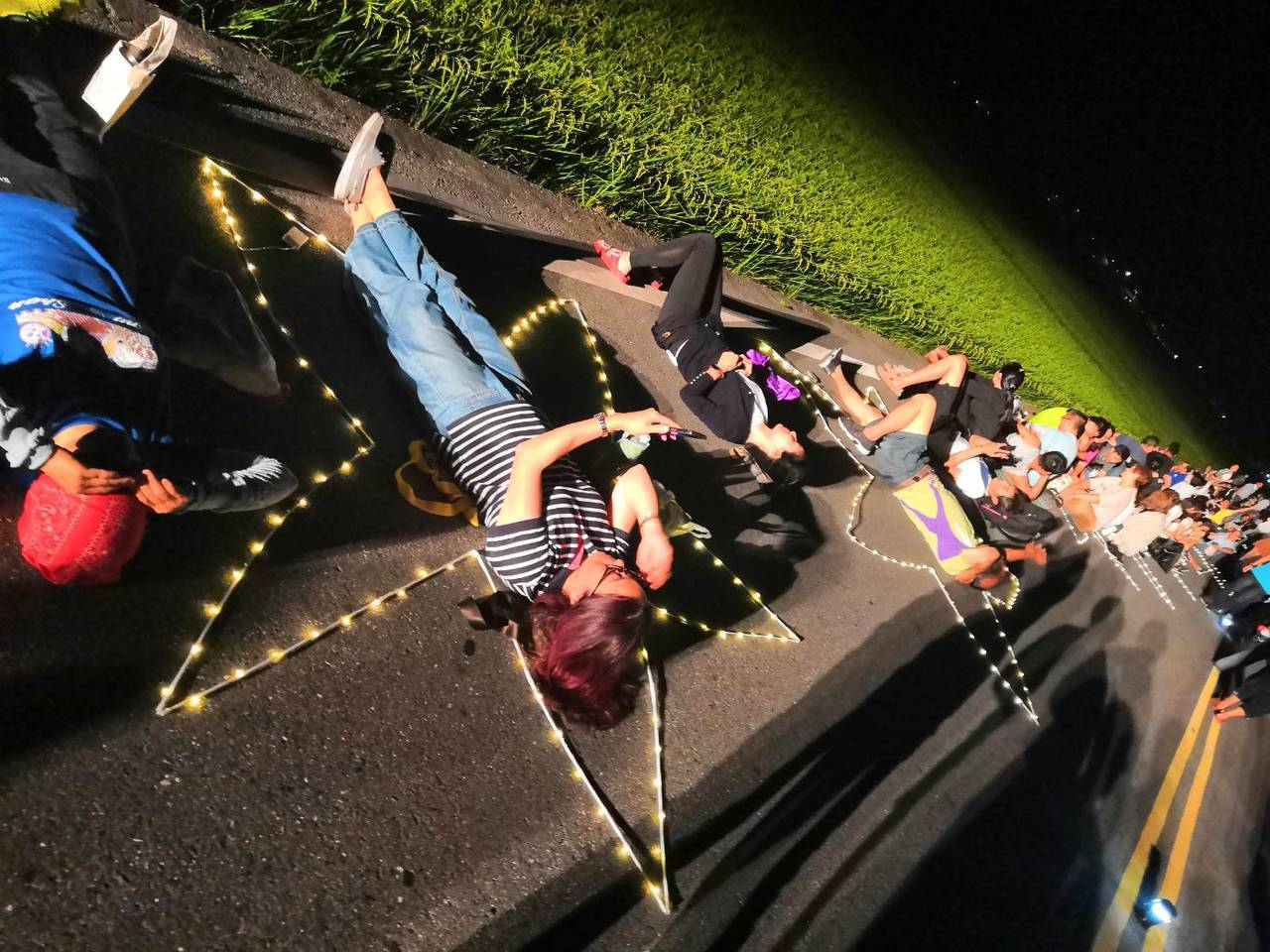 雖然晚上雲層多,星空一下出現一下消失,但仍吸引上百遊客躺在伯朗大道共襄盛舉。圖/...