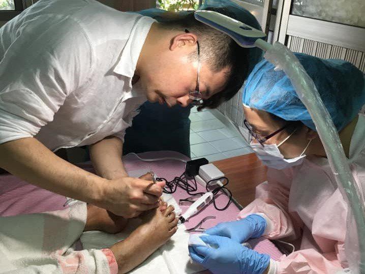 醫師嚴炯誥(左)指導健甲師替機構長輩修甲。 圖/嚴炯誥提供