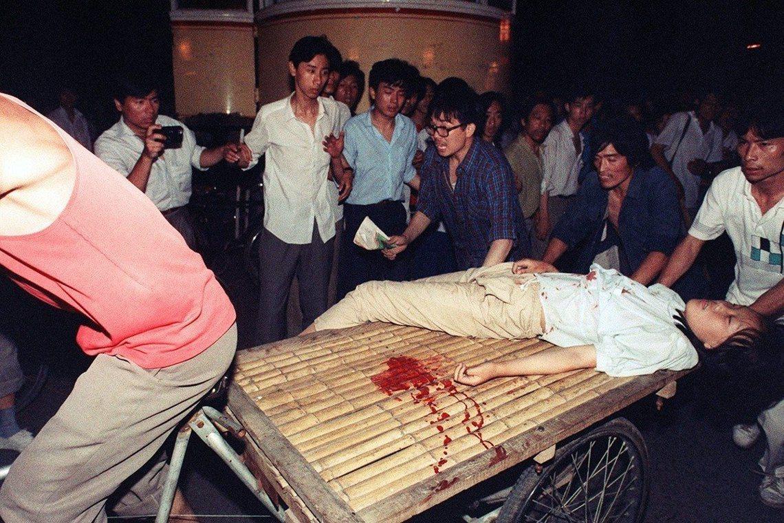 法新社 Manuel Ceneta 攝,軍警開火後,中槍受傷的群眾正被送醫急救。...