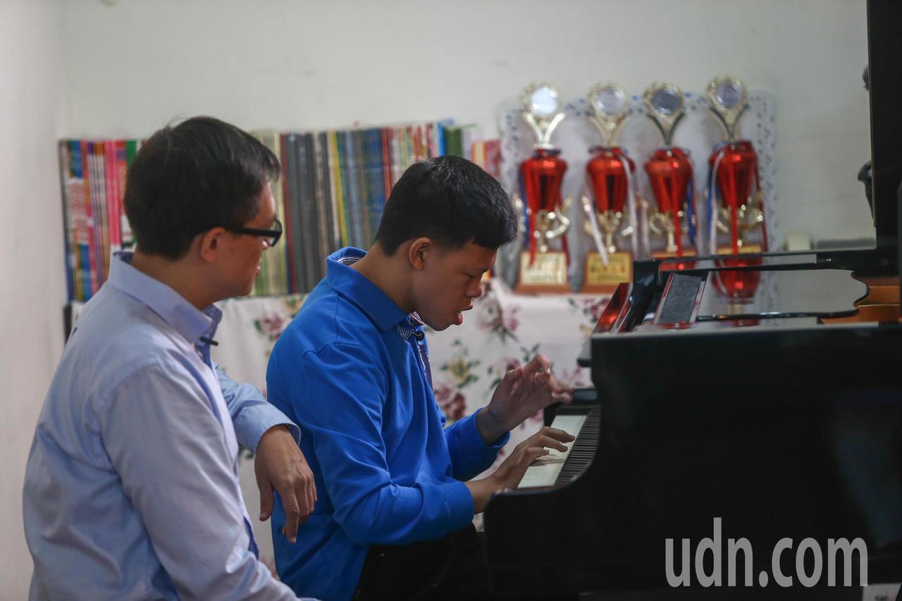 陳彥廷(右)肌肉張力低,但經過多年訓練,已可用兩個靈活的手指彈琴。記者黃仲裕/攝...