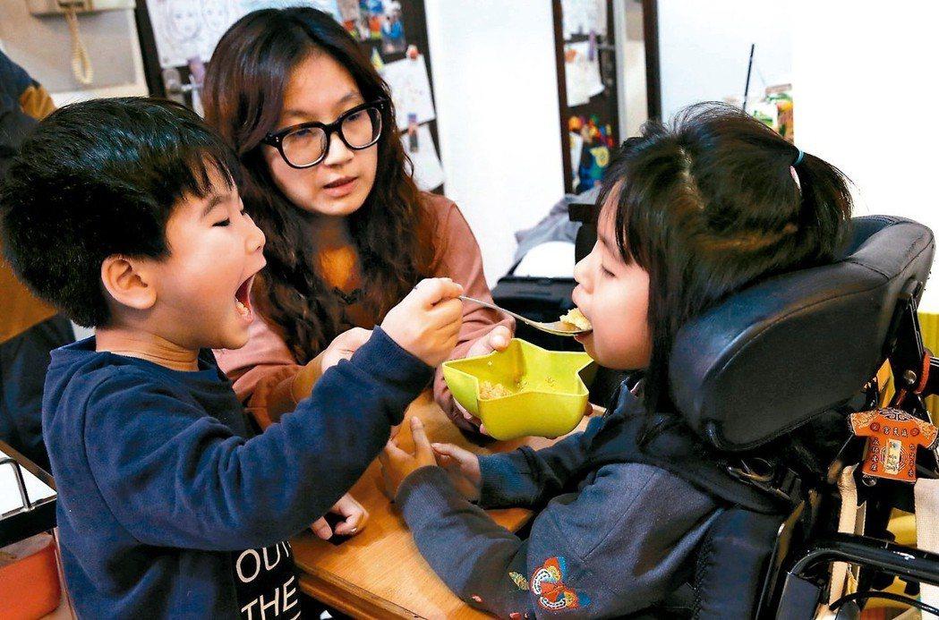 弟弟黃睦恆(左)看見媽媽鄭淑娟(中)照顧黃澄寗(右),也學著餵姐姐吃飯。 記者林...