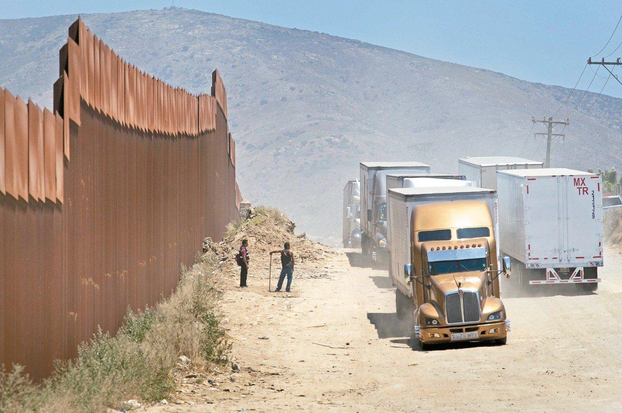 美國川普政府將對墨西哥商品加徵關稅。圖為貨車4日經過美墨邊界圍牆。 歐新社