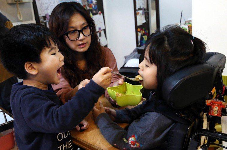弟弟黃睦恆(左)看見父母照顧姐姐澄寗,也學著餵姐姐吃飯。記者林俊良/攝影