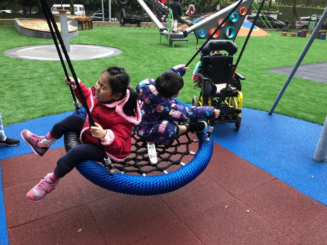 鄭淑娟聯合其他家長推動共融遊戲場,讓有身心障礙的黃澄寗可以與弟弟黃睦恆一起玩。...