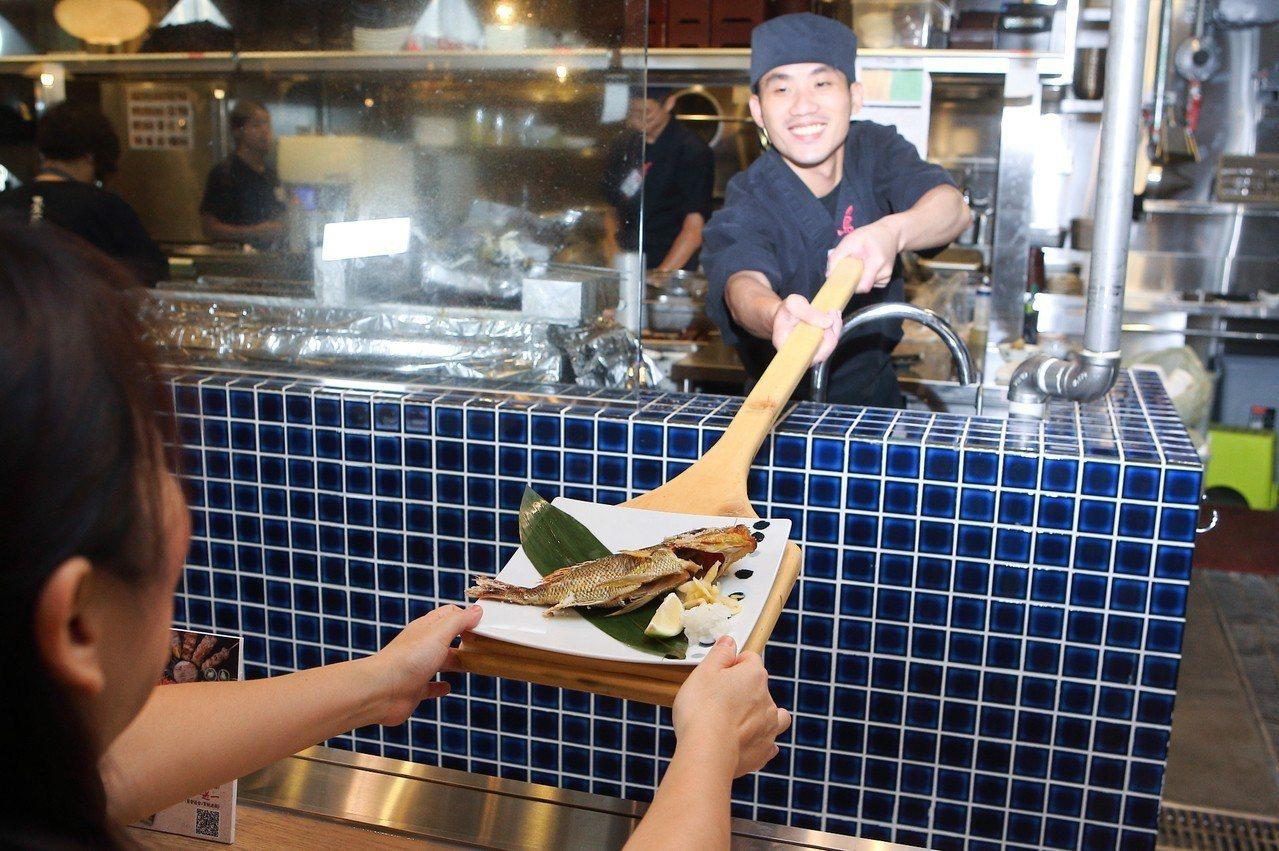 以船槳送上烤魚,乃是鳥丈端爐燒延續宮城縣的飲食傳統。記者陳睿中/攝影