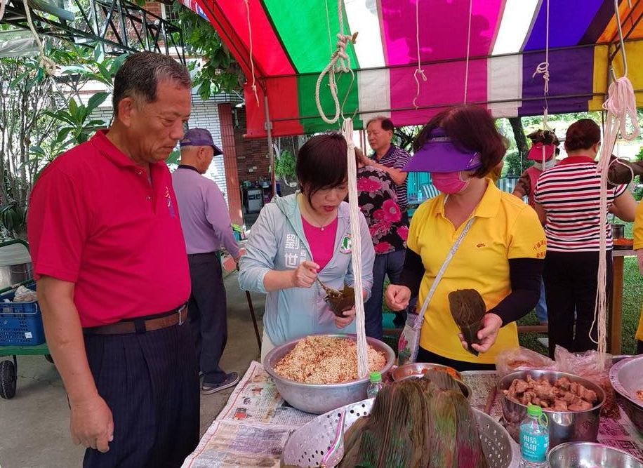 立委劉世芳(左一)到社區參加端午節活動,知道自己不太會綁粽子,趕緊幫忙炒粽米。 ...