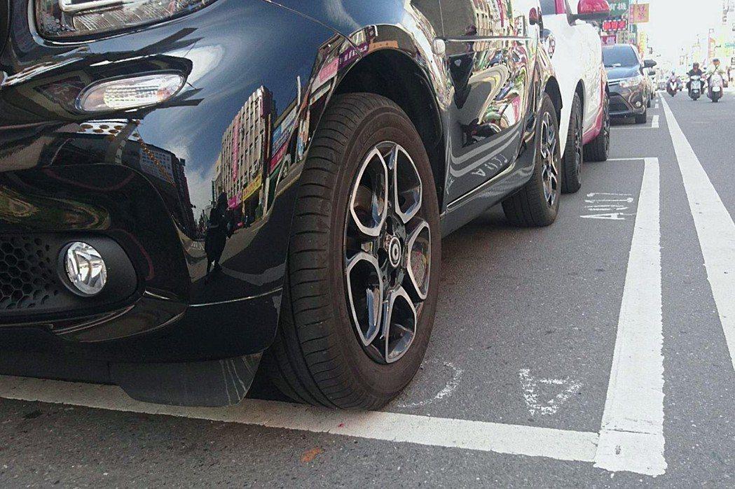 兩輛汽車竟能擠得進去同一個停車格,一格當2格用,大大省空間。圖/讀者提供