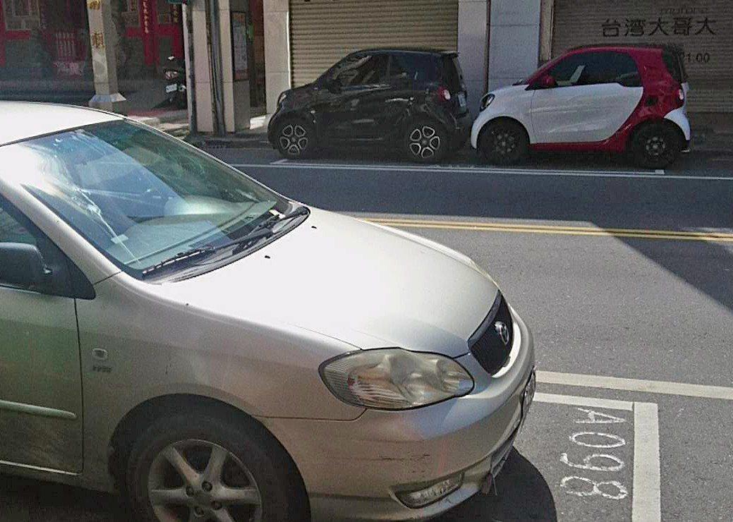 兩輛汽車竟能擠得進去同一個停車格,一格當2格用,大大省空間,路人讚賞,縣府卻不鼓...