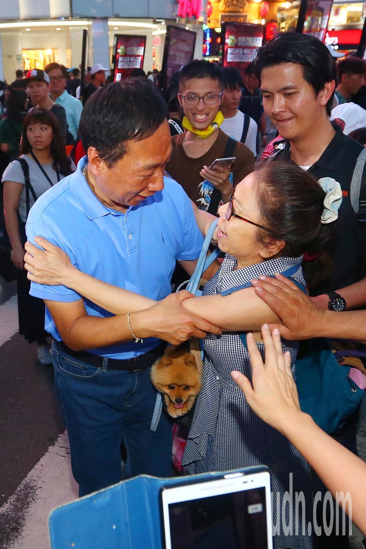 鴻海董事長郭台銘(左)傍晚到西門町發放香包,有熱情民眾上前擁抱。記者王騰毅/攝影