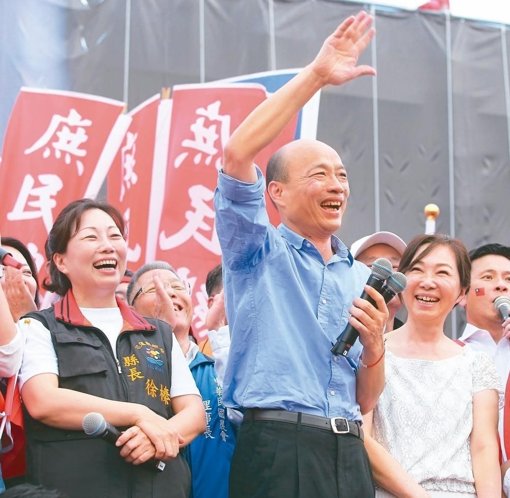 高雄市長韓國瑜(中)在花蓮造勢大會上向支持者揮手致意,妻子李佳芬(右)與花蓮縣長...