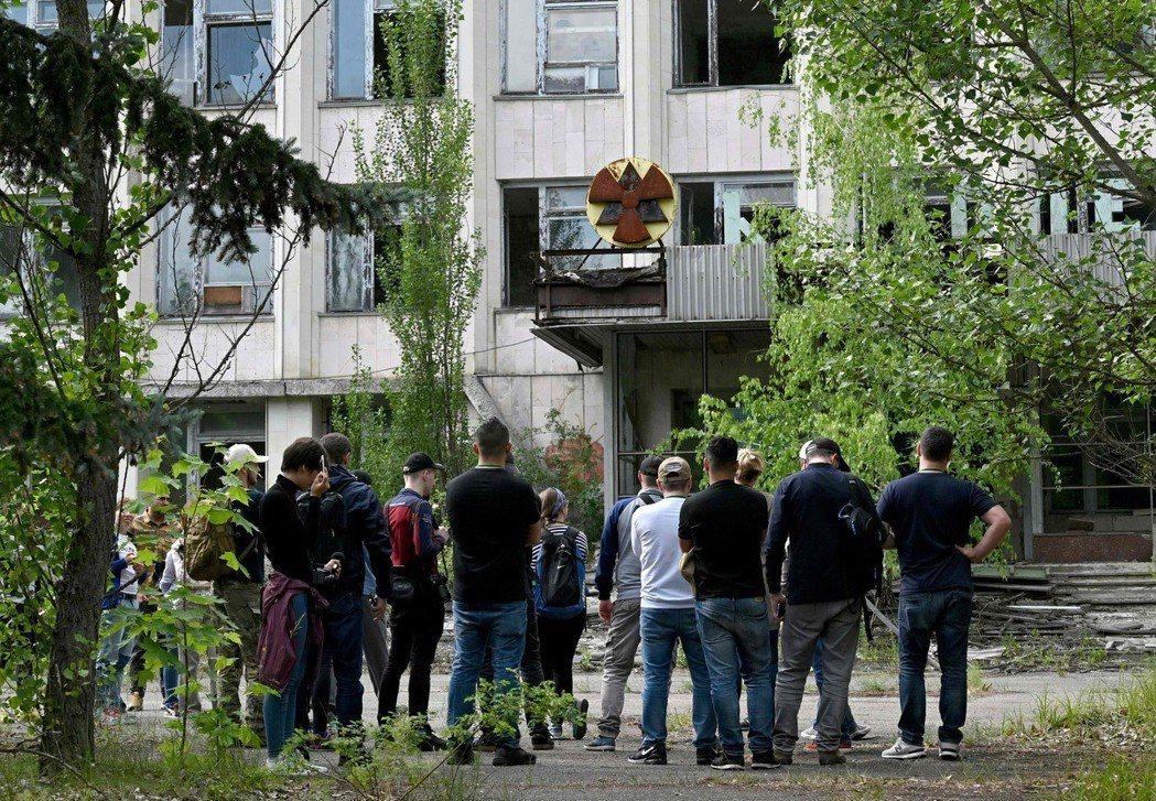 遊客正聆聽對於車諾比核災鬼城普里皮亞特市的導覽。(法新社)