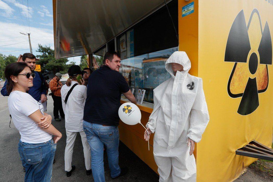 遊客參加核爆家園外景導覽,在紀念品商店外排隊購物。(歐新社)