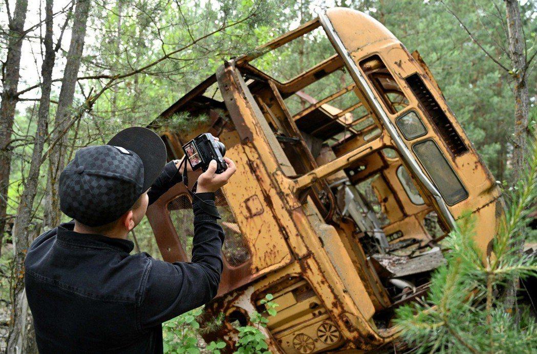 遊客在車諾比限制區導覽中,拍攝烏克蘭鬼城普里皮亞特市一個公車殘骸。(法新社)