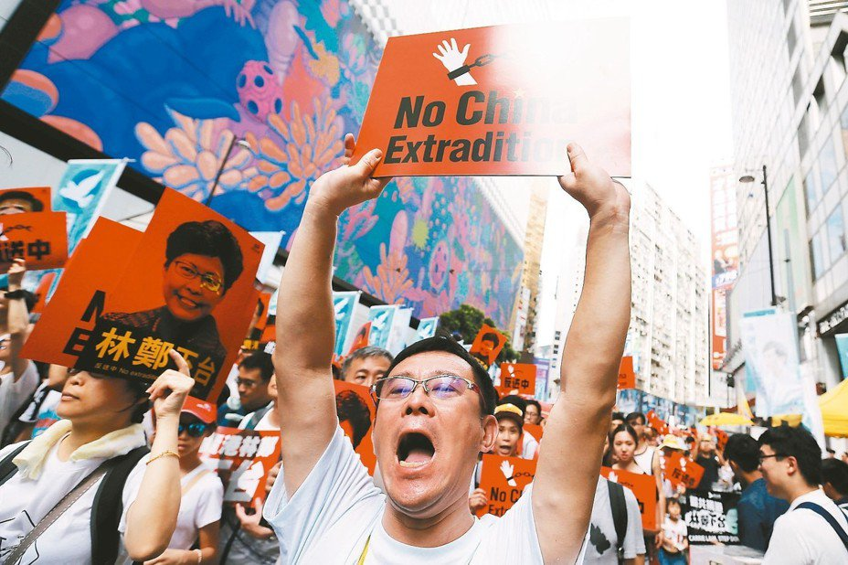香港民眾9日「反送中」大遊行,民眾高舉「反送中」標語。 路透
