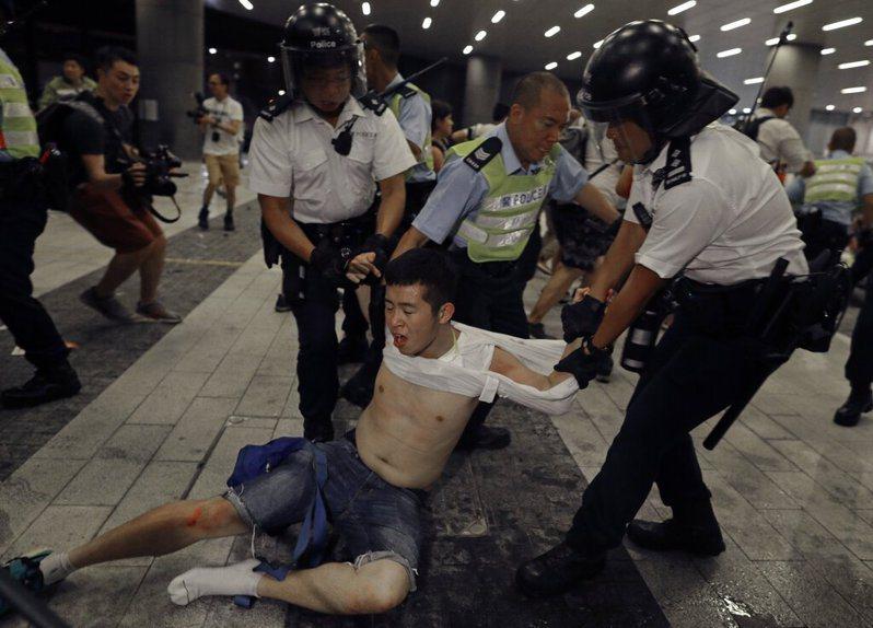香港泛民主派發起「反送中」遊行結束後,數以百計青年不願離去,凌晨後持續與警方爆發衝突,有大約百名示威者在灣仔被捕。 美聯社