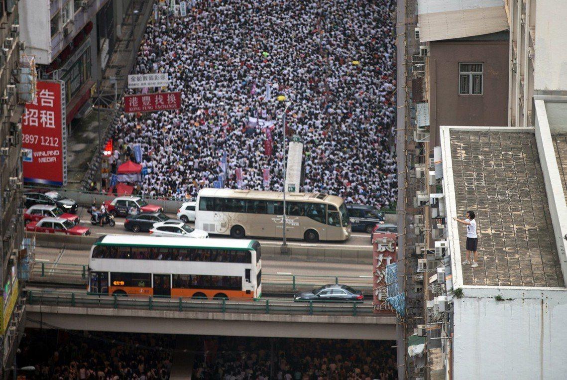 圖為9日香港「反送中」遊行,身穿白衣的群眾,從各區緩步湧入金鐘的香港特區政府總部...