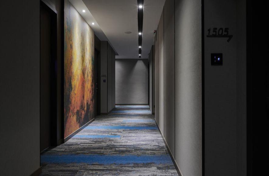 (圖)通往客房的長廊全區覆蓋精緻的藍彩地毯,與立面的巨幅壁布形成張力十足的色溫對...