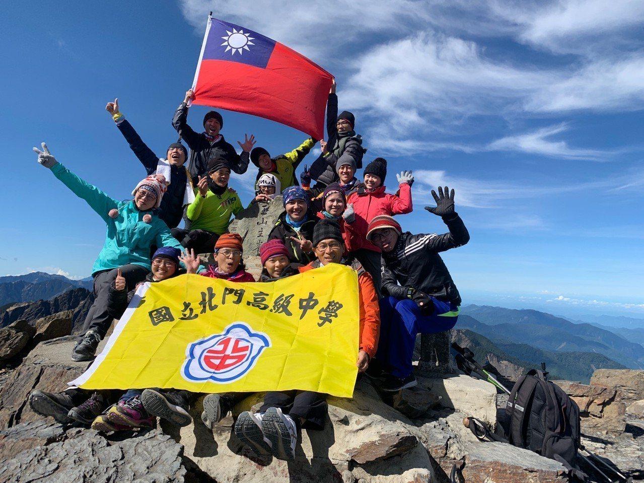 挑戰自我,北門高中師生成功攻頂玉山主峰,大夥開心拿出國旗合影。圖/北門高中提供