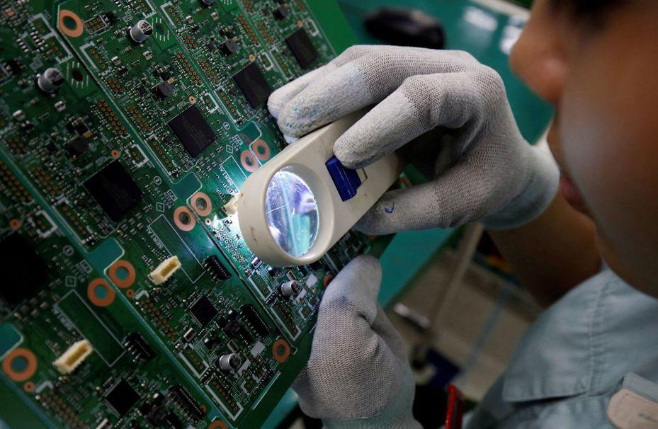 越南勞工用放大鏡檢視電路板,路透