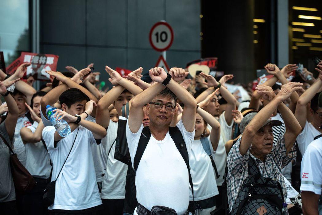 香港9日舉行「反送中」大遊行,抗議民眾皆高舉雙手比叉,代表反對修訂逃犯條例。法新...