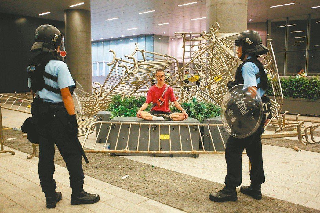 香港警察十日在立法會外看著一名靜坐抗議送中條例的民眾。 路透
