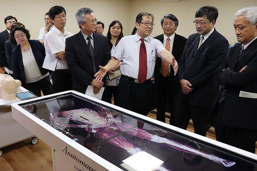 長庚大學「臨床技能與模擬中心」主任謝明儒(中)向貴賓介紹數位解剖台、高擬真模擬教...