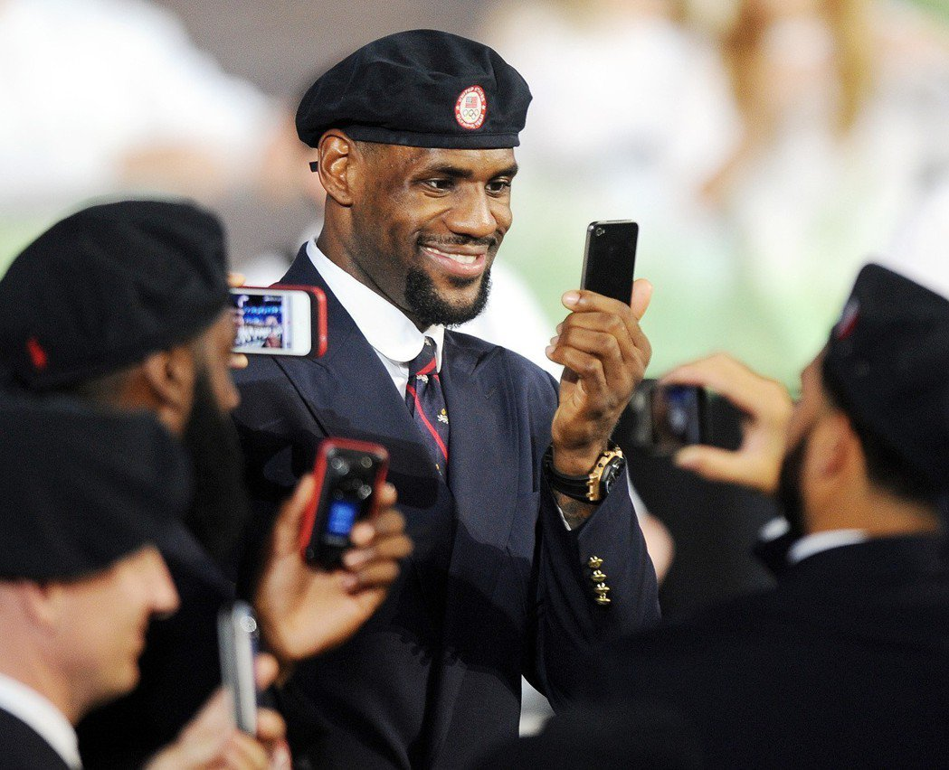 2020東奧觀賽恐不能打卡PO照了。圖為NBA球星詹姆斯參加倫敦奧運開幕式時,用...