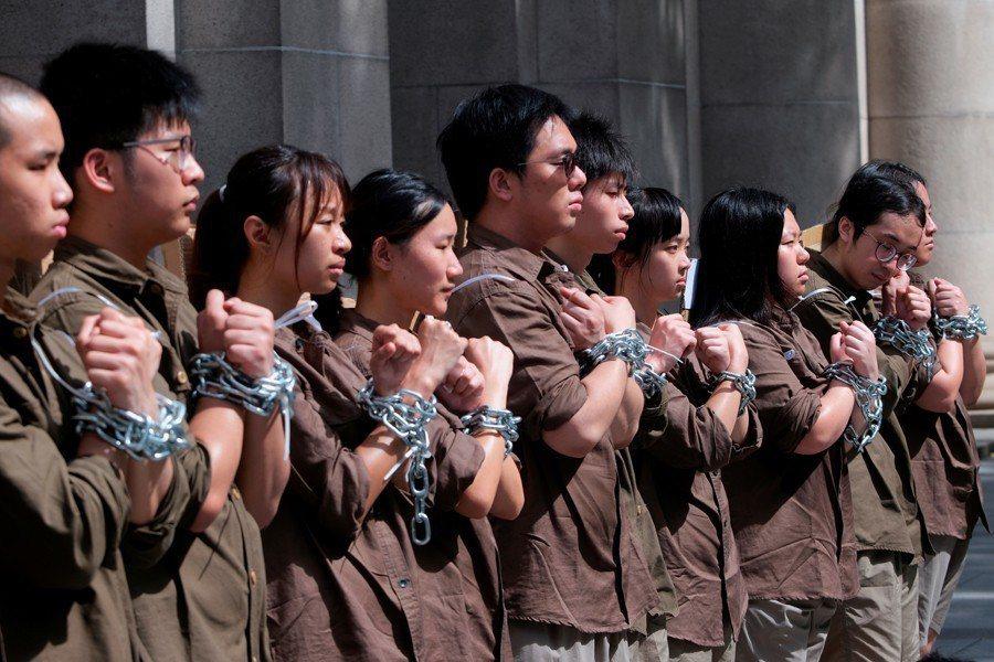 香港學生綑綁自己加入遊行行列,意在諷刺港府修改逃犯條例將使香港的司法獨立地位不再...