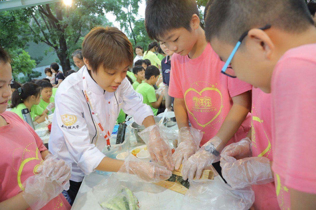 嘉藥餐旅系學生教導紅瓦厝國小學童包壽司技巧。圖/嘉藥提供