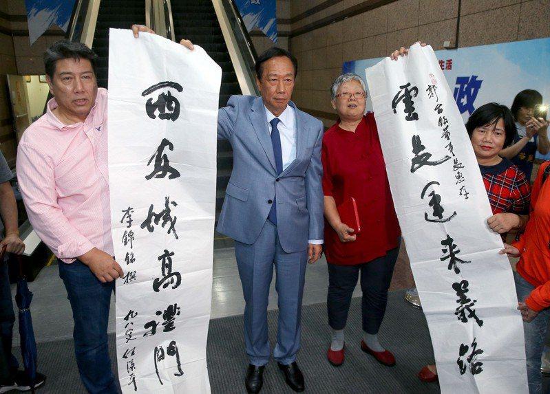 國民黨總統初選參選人郭台銘上午至中央黨部出席提名初選同志座談會,支持者送上一副對聯力挺。記者余承翰/攝影