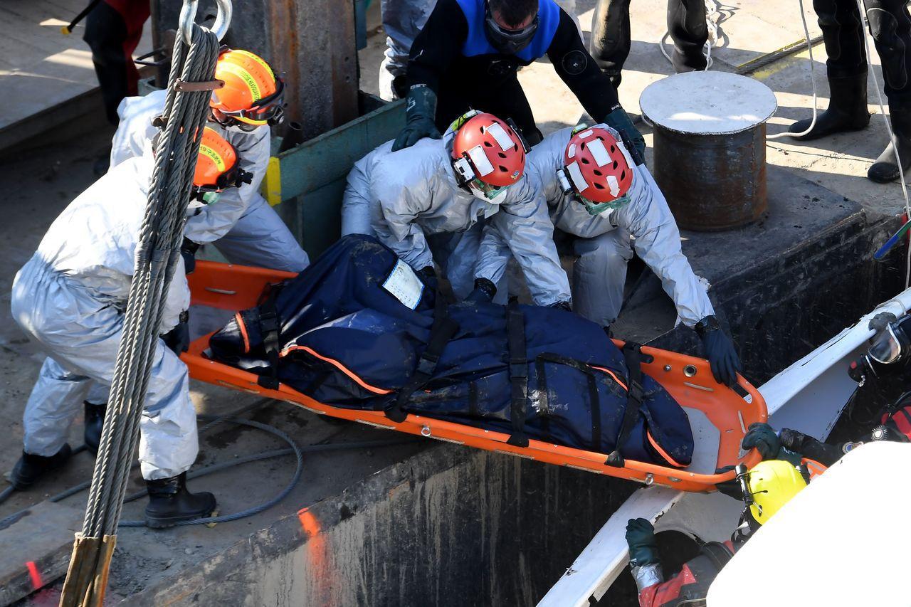 救難人員將船艙中尋獲的遺骸運出。(法新社)