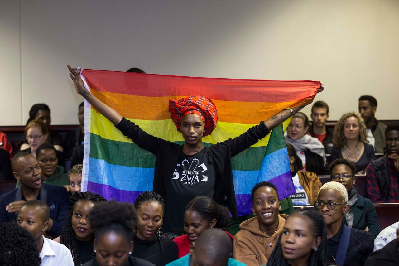 一名同性人權運動者十一日在法院旁聽席拉開彩虹旗。(法新社)