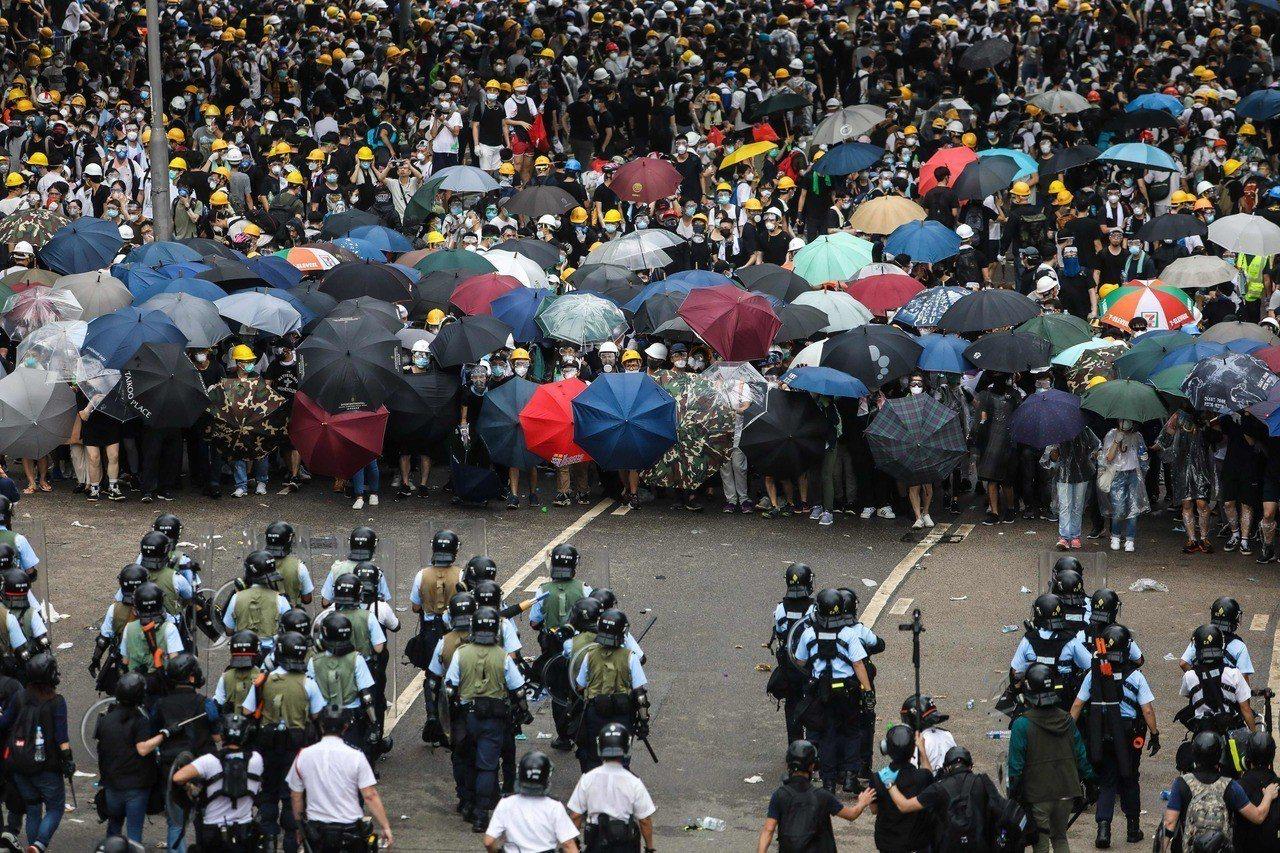 第一線示威民眾用傘阻擋將迎來的煙霧彈。法新社