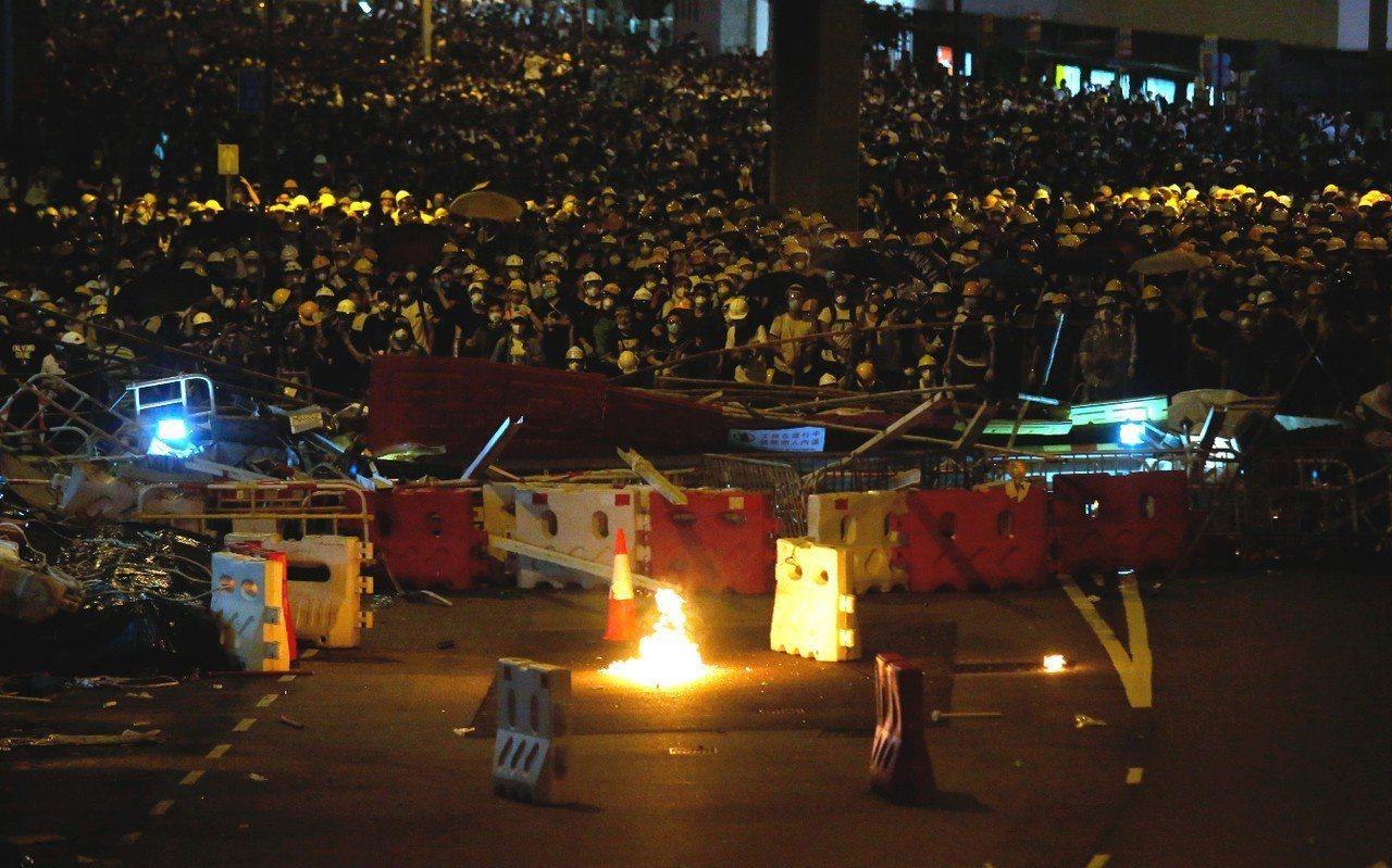 逃犯條例示威持續至晚上,有零星示威者向警方方向擲出燃燒物。 美聯社