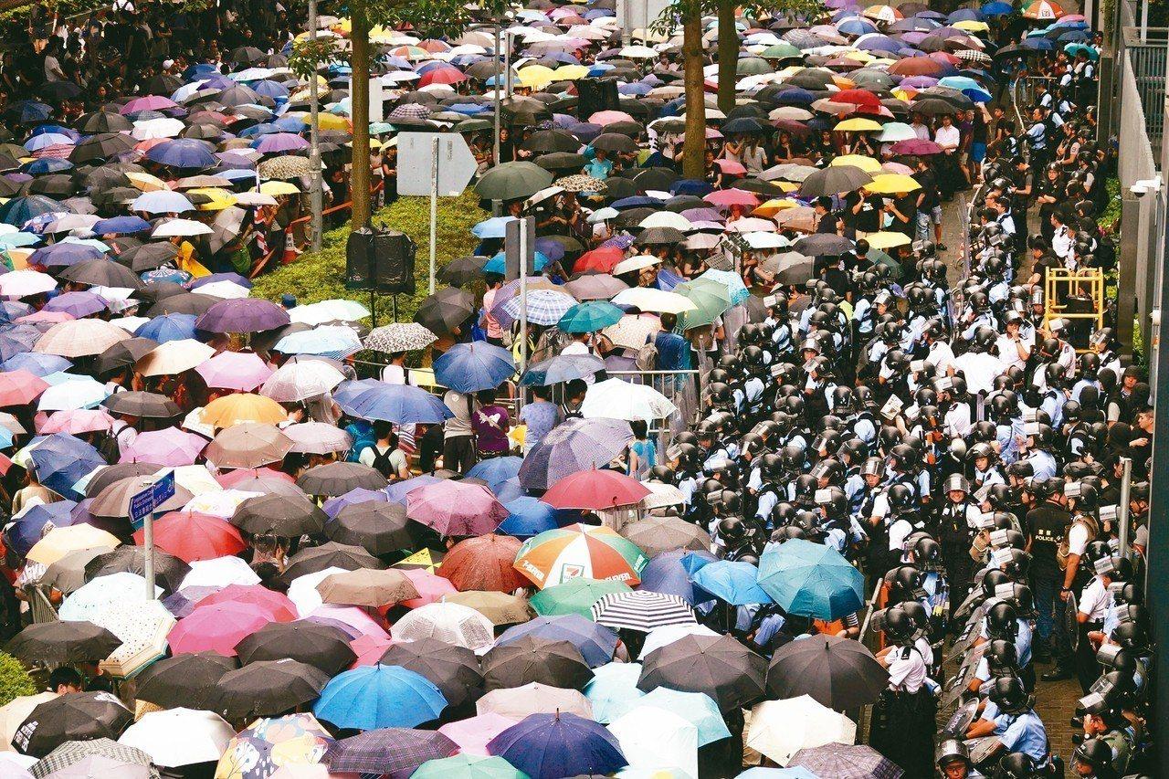 反送中遊行抗議延燒,今天上午上萬民眾聚集立法會外,與警方對峙,前排的示威者以雨傘...