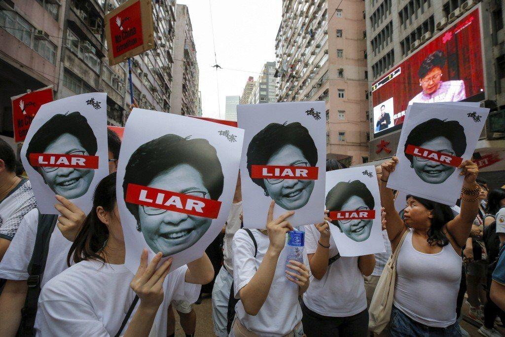 6月9日遊行群眾手持林鄭月娥照片。引起香港民眾憤怒的是,只要此法一開,香港將正式...