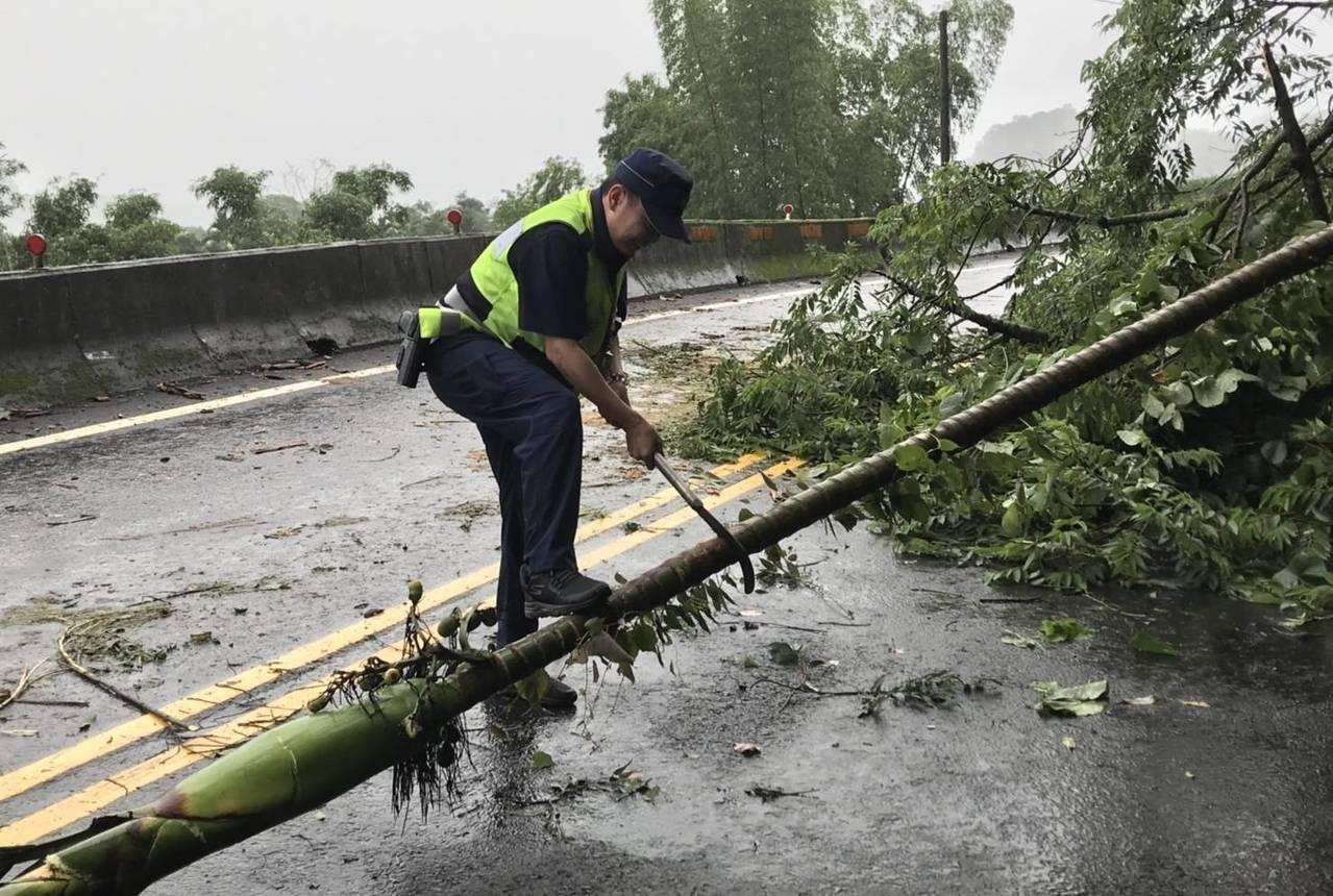 警員看到路樹傾倒,向附近民宅借來工具砍樹。圖/東勢分局提供