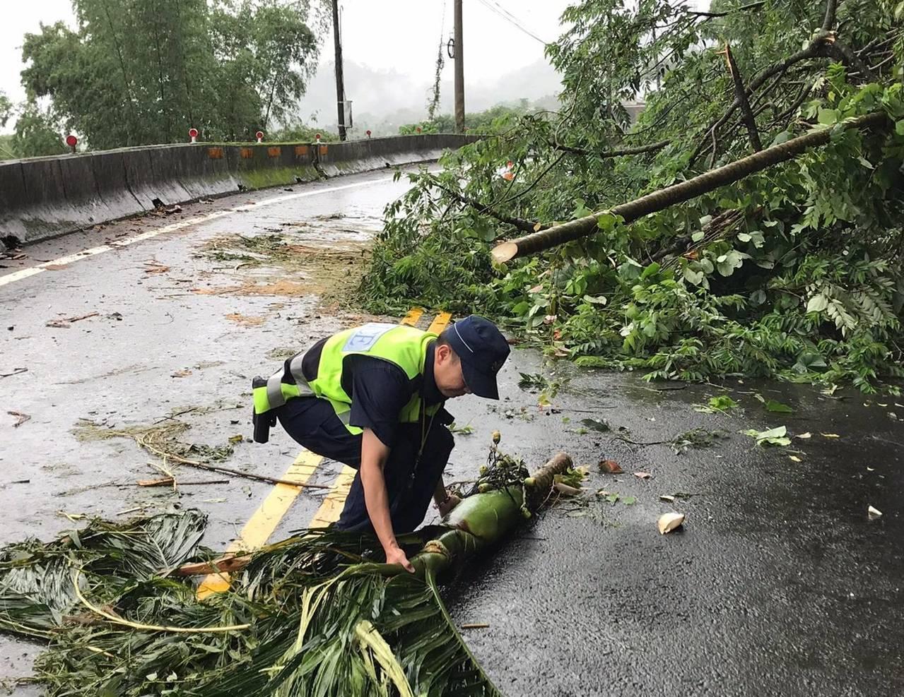 警員看到路樹傾倒,向附近民宅借來工具砍樹,排除路倒樹木。圖/東勢分局提供