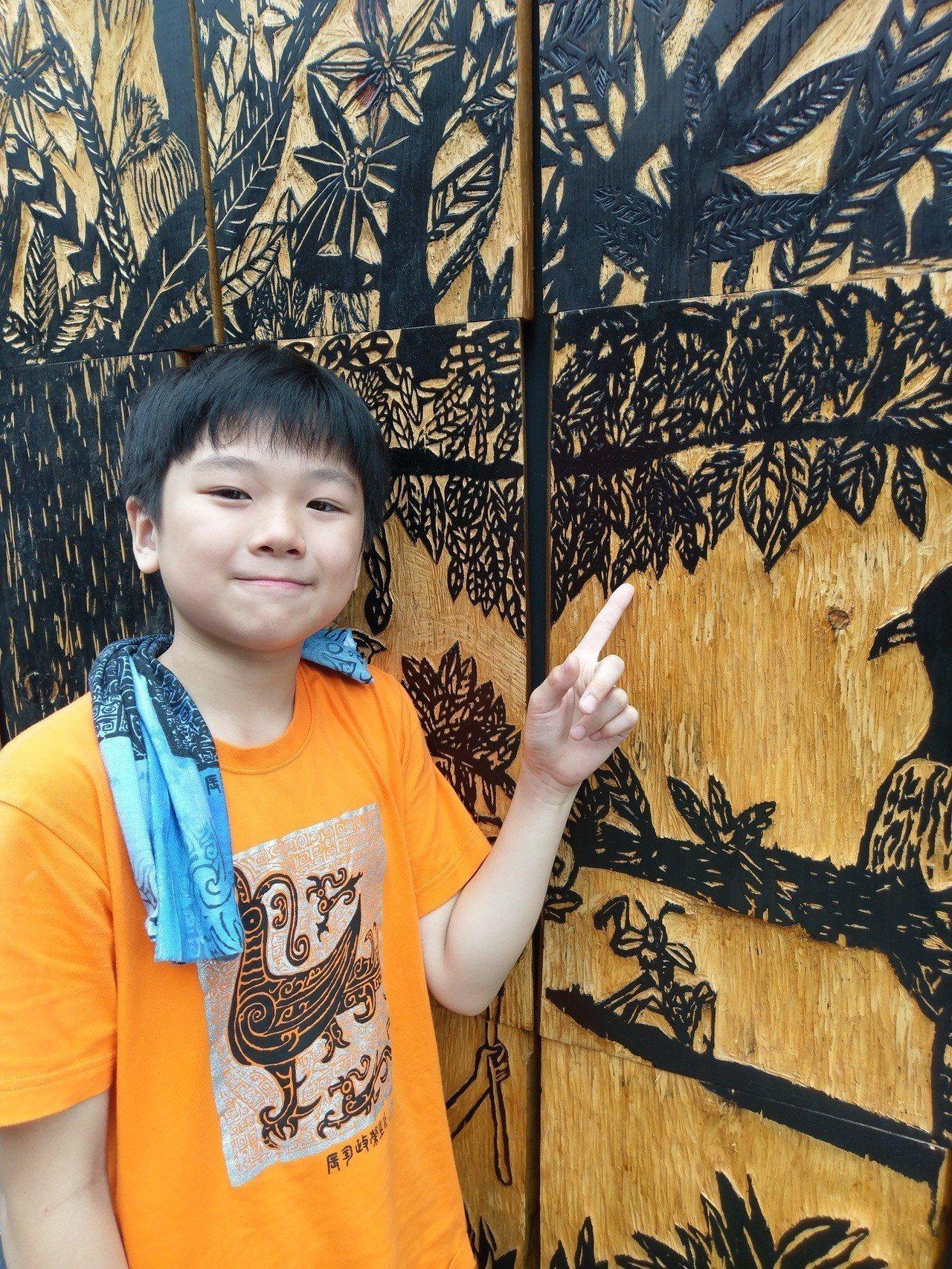 民族國小美術班學生王禾林開心地指著自己負責雕刻的木板。圖/全聯善美的文化藝術基金...