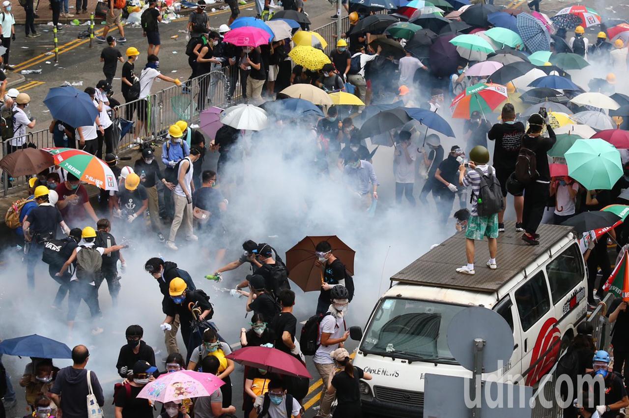 警方不停發射催淚瓦斯,試圖驅散「違法集結」的示威群眾,部分民眾咳嗽與掩住口鼻。特...