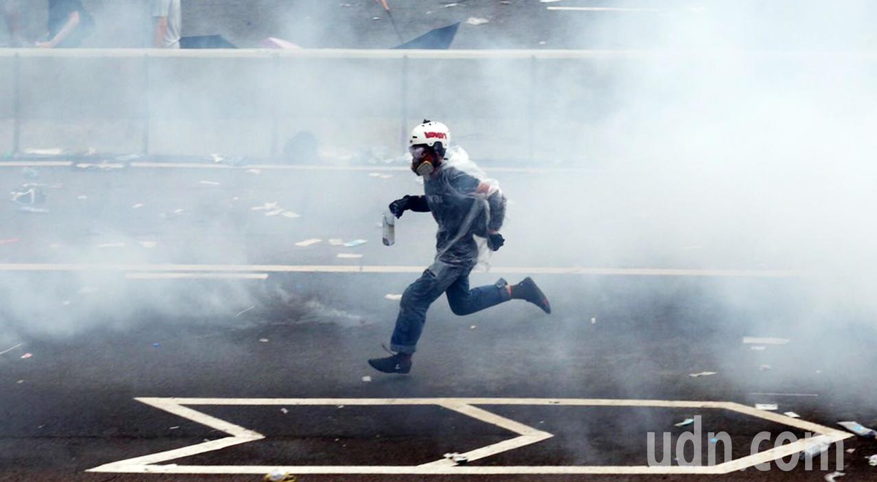 警方不停發射催淚瓦斯,試圖驅散「違法集結」的示威群眾,民眾在煙霧內逃竄。特派記者...