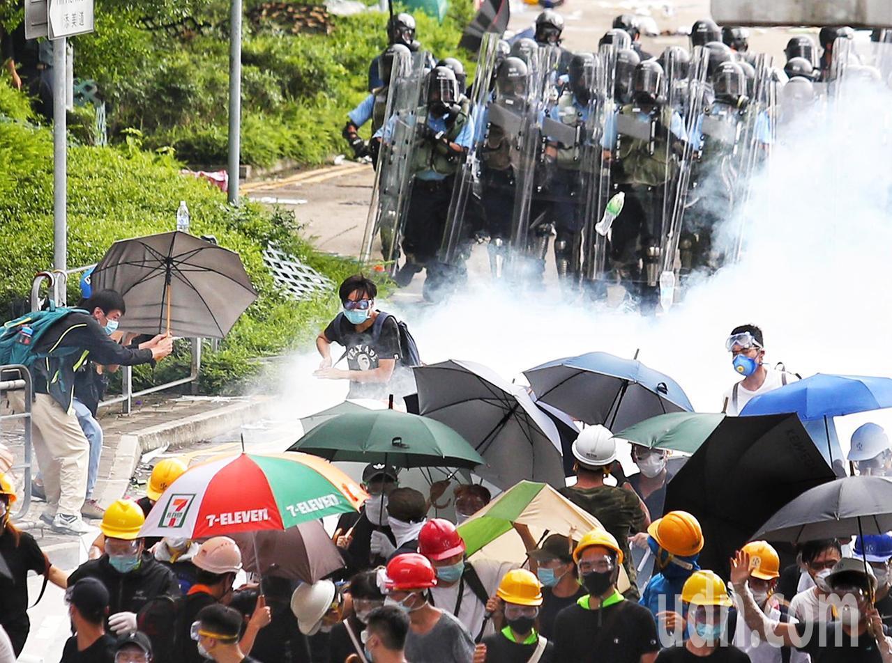 警方正不停發射催淚瓦斯,試圖驅散「違法集結」的示威群眾,群眾以傘抵擋向後撤退。特...