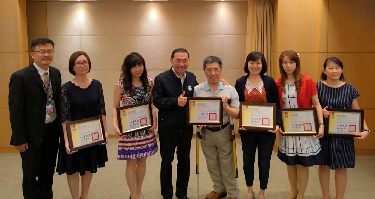 獲得教育部閱讀推手個人獎的新北市光華國小教師蔡正雄(右4),昨在於市政會議獻獎給...