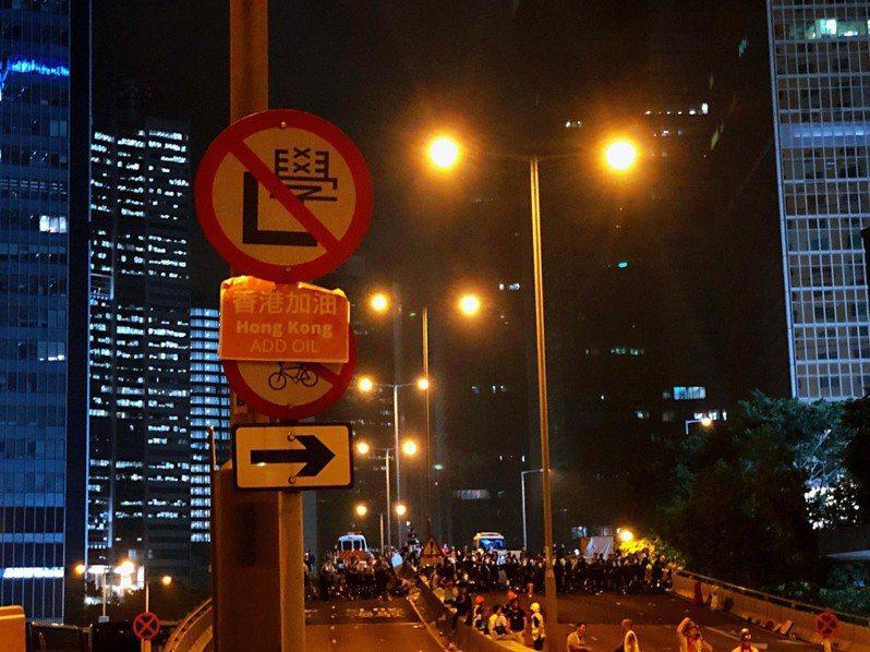 深夜的中環,反送中的民眾與警察的對峙,「香港加油」的標語貼在兩者之間。記者顏甫珉/攝影