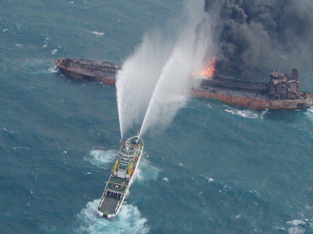 伊朗桑吉號油輪在上海外海跟其他船相撞後起火燃燒,圖為救援船隻灑水救火畫面。 (路...