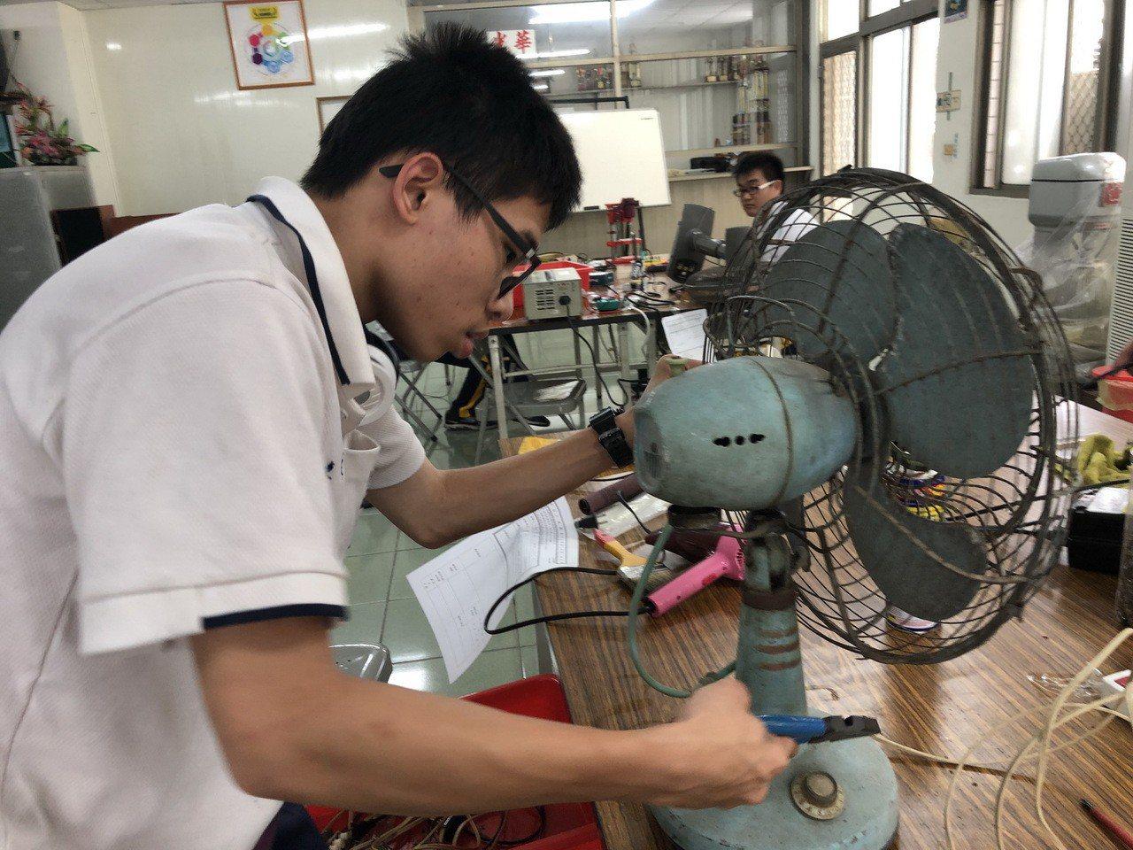 中山工商家電維修中心師生利用假日,為屏東的弱勢戶免費修理家電。圖/中山工商提供