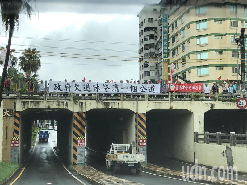 台南市退警協會成員近百人上午10時,在台南市地下道天橋,全國同步懸掛「蔡政府欠退休警消一個公道」白布條,揮舞國旗,高呼口號。記者邵心杰/攝影